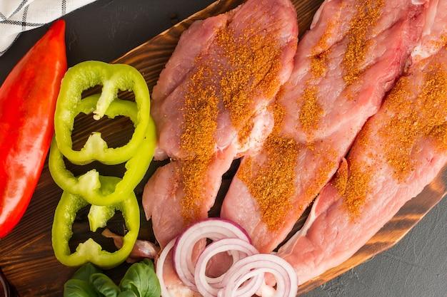 Vorbereitet zum backen von frischen koteletts aus ausgewähltem fleisch mit paprika, zwiebeln auf dem küchenbrett. ansicht von oben. winkel schließen.