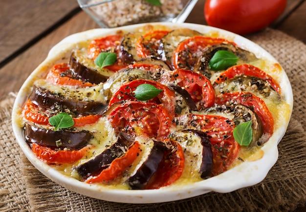 Vorbereitete auflaufform rohe auberginen mit mozzarella und tomaten