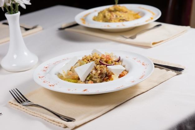 Vorbereitete gerichte, serviert an einfachen gedecks auf einem restauranttisch mit akzenten in einer weißen blumenvase