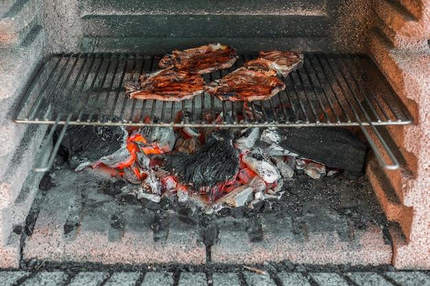 Vorbereitete schweinefleischfilets, die über kohlen im grill gekocht werden