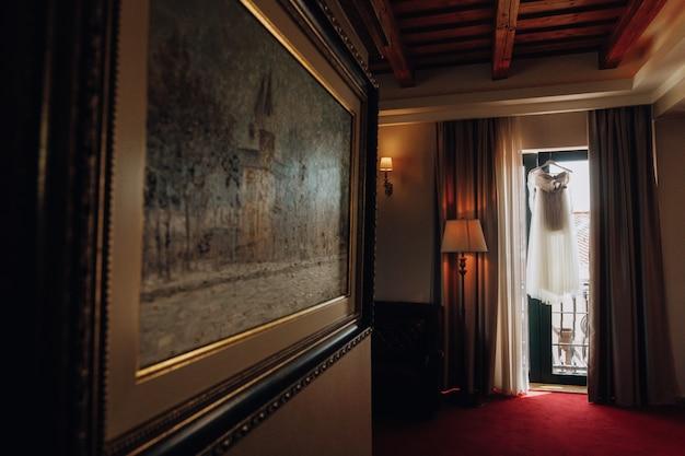 Vorbereitetes hochzeitskleid in einem leeren raum des hotels
