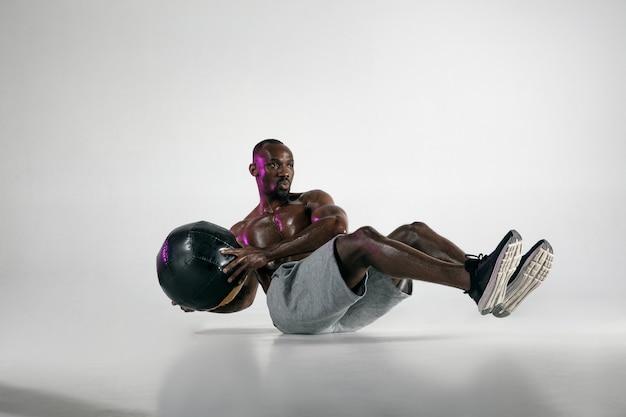 Vorbereitung auf das beste. junge afroamerikanische bodybuilderausbildung über grauem hintergrund. muskulöses einzelnes männliches modell in sportbekleidung mit dem ball. konzept von sport, bodybuilding, gesundem lebensstil.