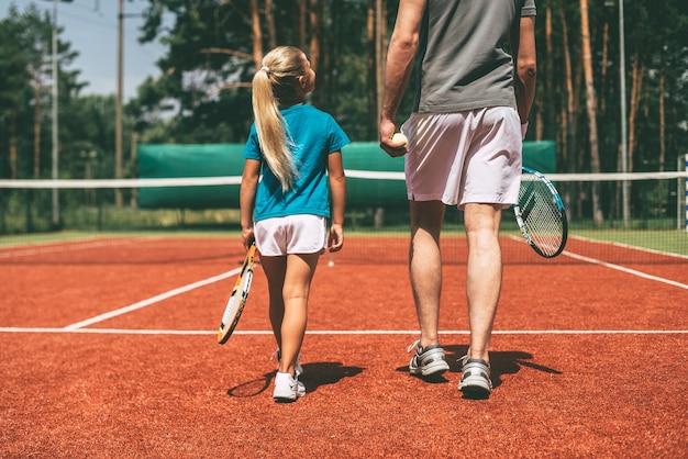 Vorbereitung auf das große spiel. rückansicht eines kleinen blonden mädchens in sportkleidung, das tennisschläger trägt und ihren vater ansieht, der in ihrer nähe durch den tennisplatz geht?