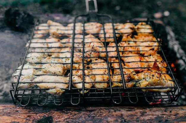 Vorbereitung auf dem grill. gericht mit gebratenem fleisch auf verschwommenem gras. heißes leckeres rauchiges barbecue-essen bei kohlen und verbranntem brennholz. kochen in flammen im freien.