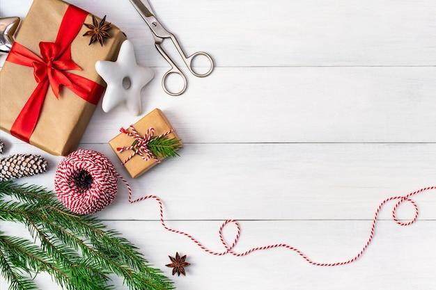 Vorbereitung auf die feiertage, verpacken von geschenken, draufsicht mit kopierraum. hintergrund mit geschenkboxen in bastelpapier, gestreiftem seil, festlichen keksen und einem zweig eines weihnachtsbaumes auf einem weißen holztisch.