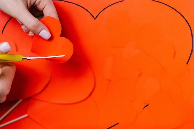 Vorbereitung auf ein romantisches abendessen. frauenhände schneiden mit einer schere ein rotes herz. einfarbiger roter hintergrund Premium Fotos