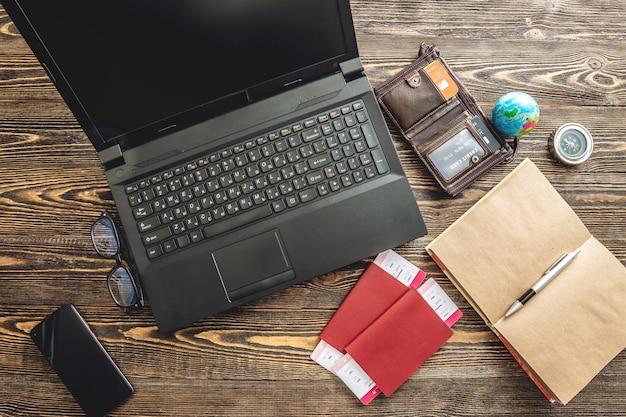 Vorbereitung auf eine aufregende reise. buchung von flügen und bezahlen mit einer kreditkarte unter verwendung eines laptops auf einem hölzernen hintergrund