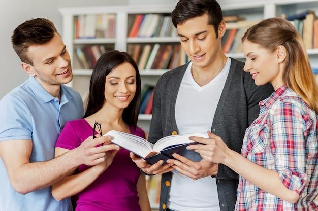 Vorbereitung auf ihre abschlussprüfungen. vier fröhliche studenten, die zusammen ein buch lesen, während sie in einer bibliothek gegen ein bücherregal stehen