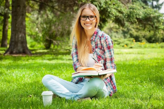 Vorbereitung auf prüfungen im freien. schöne junge studentin, die etwas in einen notizblock schreibt, während sie in einem park sitzt