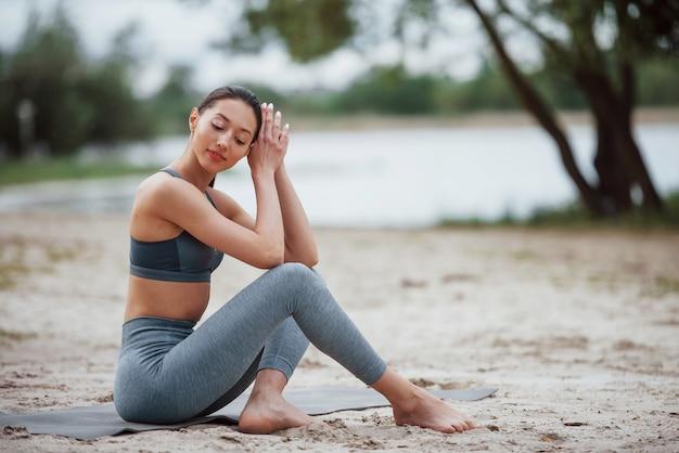 Vorbereitung auf übungen. brünette mit schöner körperform in sportlicher kleidung haben fitness-tag am strand