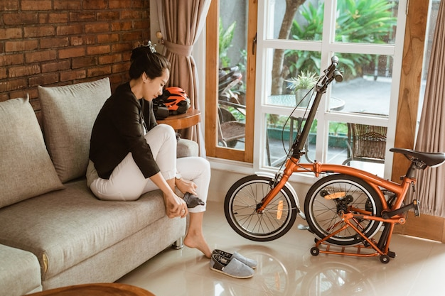 Vorbereitung der asiatischen arbeiterin, die auf dem sofa sitzt und socken trägt