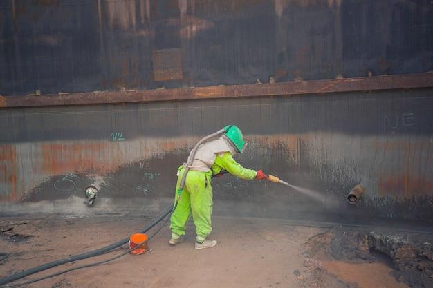 Vorbereitung der oberflächenkorrosionsplatte für weibliche arbeiter durch sandstrahlen des tankinnenöls