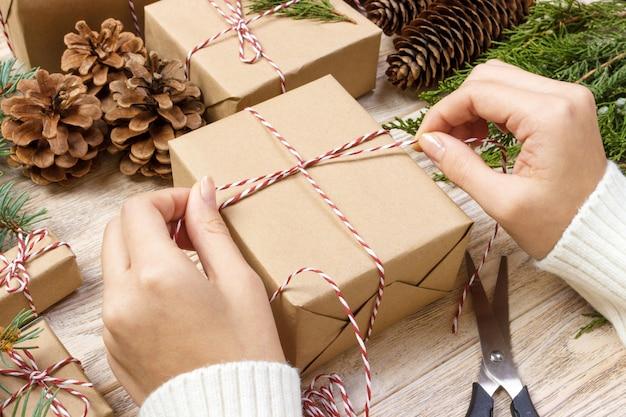 Vorbereitung der weihnachtsgeschenke. geschenkbox eingewickelt im gestreiften schwarzweiss-papier, in einer kiste voll kiefernkegeln und in weihnachtsspielwaren und in verpackungsmaterialien auf einem weißen hölzernen alten hintergrund