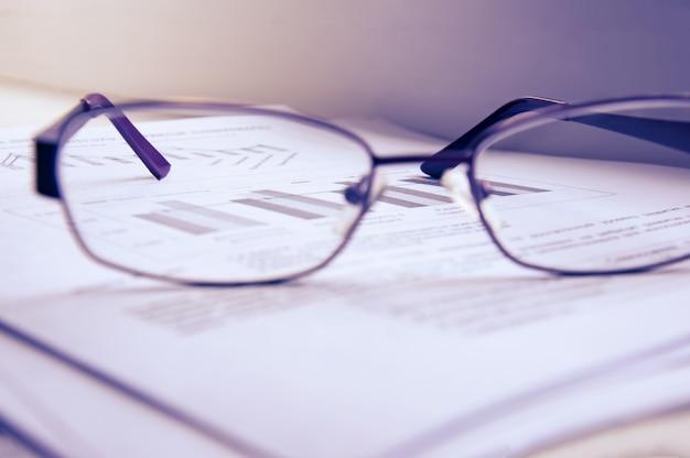 Vorbereitung des geschäftsberichts. ein stapel von dokumenten, ein notizbuch und gläser auf dem tisch.