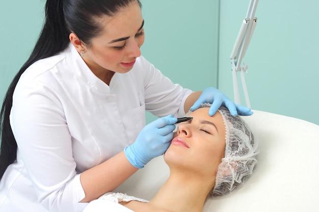 Vorbereitung des gesichts des patienten auf einen kosmetischen eingriff.