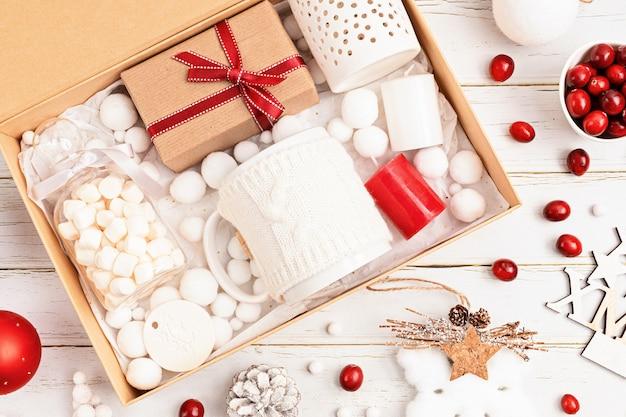 Vorbereitung des pflegepakets, saisonale geschenkbox mit marshmalow, kerzen und tasse in roten und weißen farben. personalisierter umweltfreundlicher korb für familie und freunde zu weihnachten. draufsicht, flach liegen
