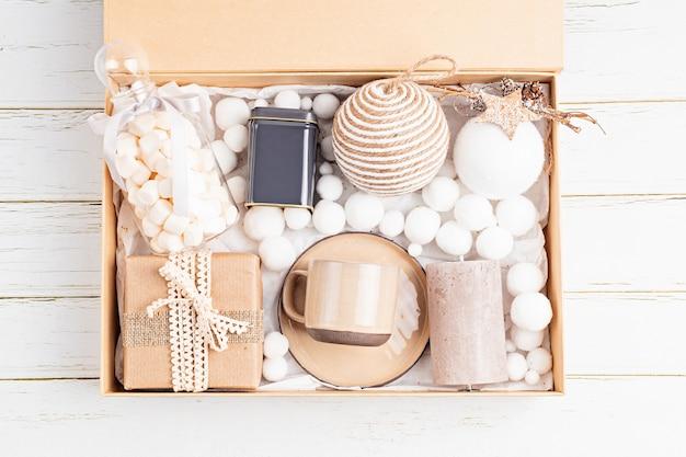 Vorbereitung des pflegepakets, saisonale geschenkbox mit tee-, kerzen-, tassen- und weihnachtsschmuck. personalisierter umweltfreundlicher korb für familie und freunde zu weihnachten. draufsicht, flach liegen