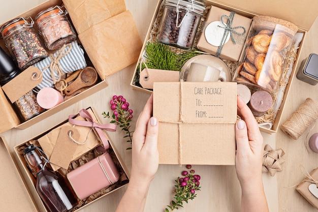 Vorbereitung des pflegepakets und der saisonalen geschenkbox mit kaffee, keksen, kerzen, gewürzen und tassen