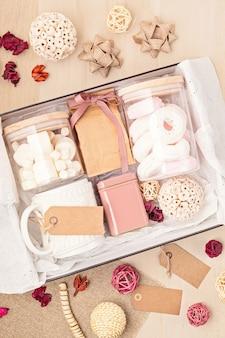 Vorbereitung des pflegepakets und der saisonalen geschenkbox mit marshmallow-, tee-, kaffee- oder kakaobox und weihnachtsschmuck