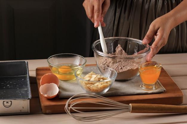 Vorbereitung, die geschmolzene schokolade und kakaopulver in einer schüssel mischt, um teig für köstlichen brownie-kuchen auf rustikalem holztisch mit schneebesen zu machen