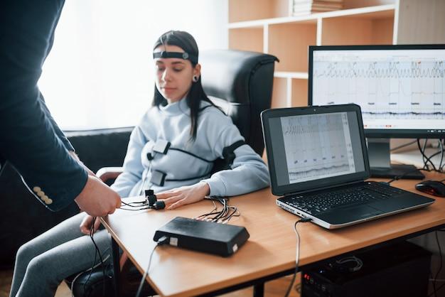 Vorbereitung, elektroden an den fingern anbringen. mädchen geht lügendetektor im büro vorbei. fragen stellen. polygraphentest
