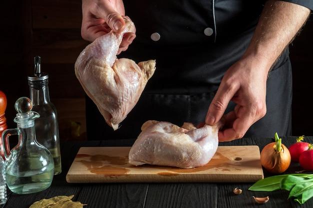 Vorbereitung für das kochen von hähnchenschenkeln in der restaurantküche chefkoch oder koch hält rohes hähnchenschenkel