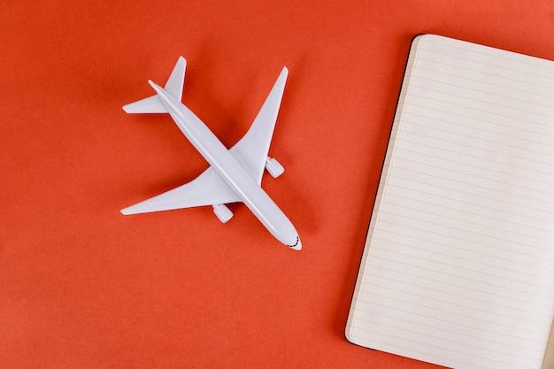 Vorbereitung für das reisekonzept mit leeren papiernotizen auf flugzeugmodellflugzeug