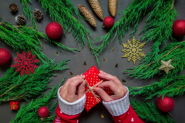 Vorbereitung für den feiertag, geschenke an den händen weihnachtszubehör-kerzenbaum einwickelnd
