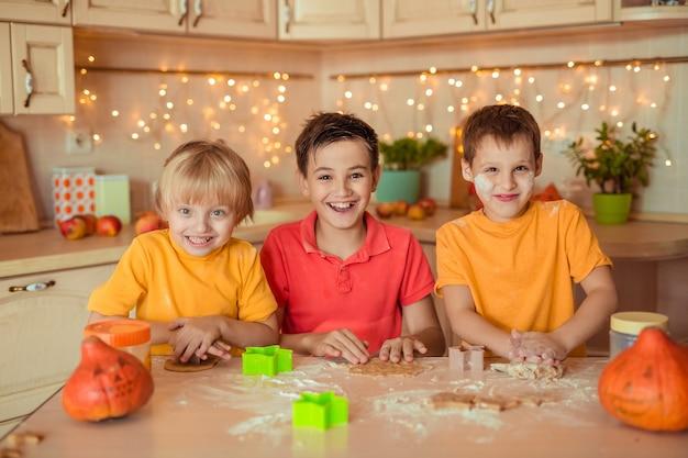 Vorbereitung für den feiertag halloween. drei fröhliche kinder machen in der küche kekse
