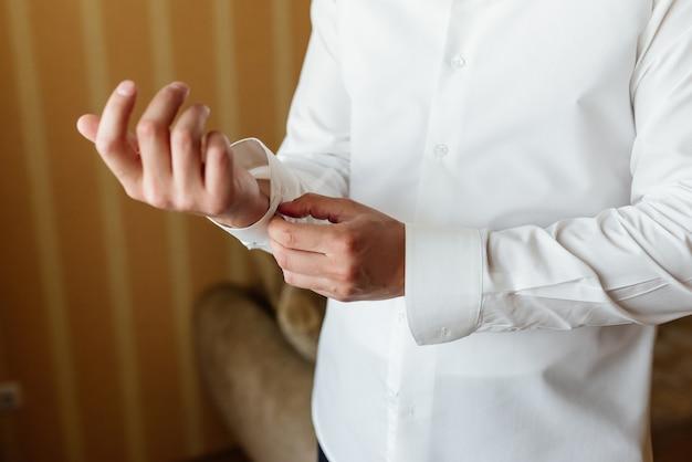 Vorbereitung für die hochzeit. knöpfende manschettenknöpfe des bräutigams auf weißem hemd vor hochzeit.