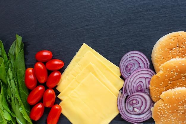 Vorbereitung für die zubereitung eines hamburgers, alle zutaten: käse, salat, tomate, zwiebel, brötchen liegen auf einem schwarzen steinhintergrund. von oben betrachten.