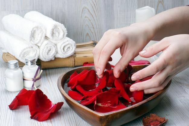 Vorbereitung für ein spa-verfahren für hände mit blütenblättern aus roten rosen und weißen accessoires