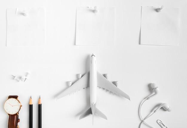 Vorbereitung für reisendes konzept, uhr, flugzeug, bleistifte, notiertes papier, kopfhörer