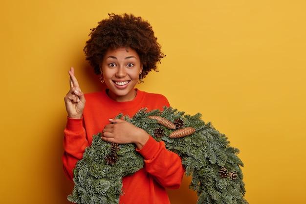 Vorbereitung für winterferien und festliche inneneinrichtung. fröhliche afroamerikanerin drückt die daumen, wünscht sich, posiert mit weihnachtskranz