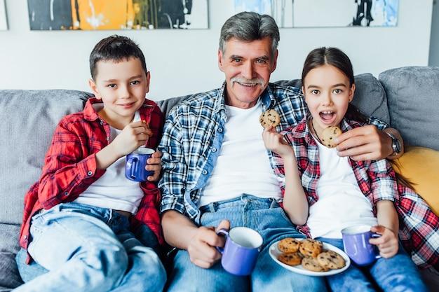 Vorbereitung vor dem film. großvater mit zwei hübschen enkelkindern, die plätzchen essen