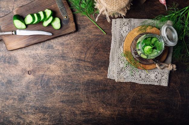 Vorbereitung zum beizen von gurken. hausgemachte gurken geschnitten in scheiben mit dill und knoblauch auf rustikalem sperrholzhintergrund. gemüse für den winter ernten. draufsicht. platz für text.
