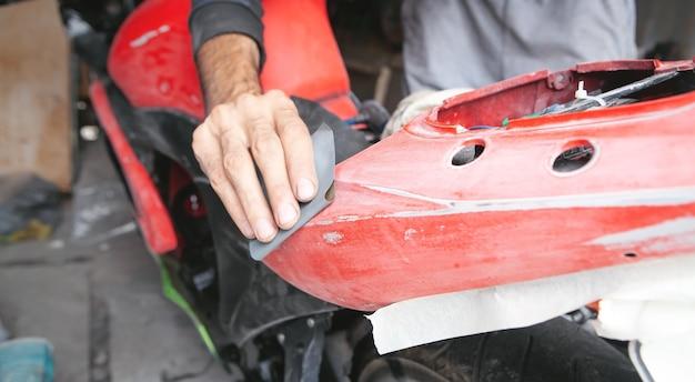 Vorbereitung zum lackieren eines motorrads. geben sie ein schleifpapier ab