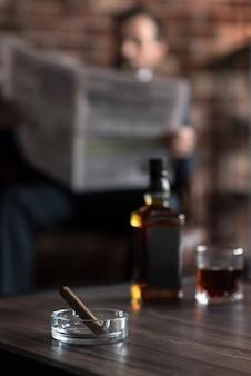 Vorbereitung zum rauchen. selektiver fokus eines transparenten glasaschenbechers mit einer zigarre auf dem tisch neben der flasche whisky