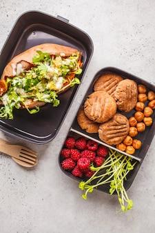 Vorbereitungsbehälter der gesunden mahlzeit mit quinoa angefüllten süßkartoffeln, plätzchen und beeren, obenliegender schuss.