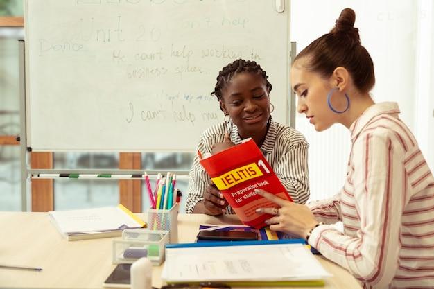 Vorbereitungsbuch. aufmerksames mädchen, das in halbposition sitzt und lehrbuch liest reading