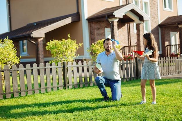 Vorbild. angenehmer, liebevoller vater, der seiner geliebten kleinen tochter zeigt, wie man papierflugzeuge startet, während man mit ihr im hinterhof spielt