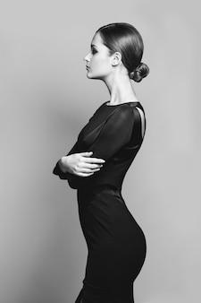 Vorbildliche aufstellung der schönheit im eleganten kleid im studio