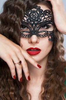 Vorbildliche frau der schönheit, die venetianische maskeradekarnevalsmaske an der partei über dunklem hintergrund des feiertags mit magischen sternen trägt.