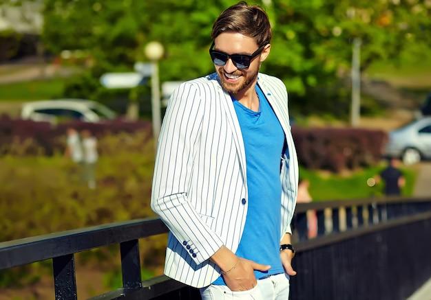 Vorbildlicher mann des jungen stilvollen überzeugten glücklichen hübschen geschäftsmannes im blauen klagenstofflebensstil in der straße in der sonnenbrille
