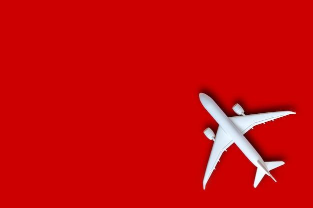 Vorbildliches flugzeug, flugzeug auf hintergrund der roten farbe mit kopienraum