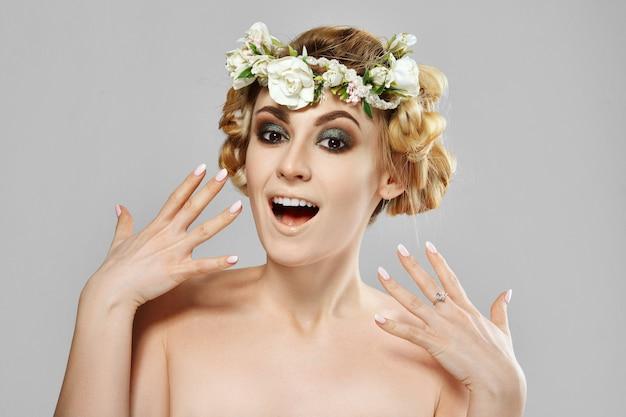 Vorbildliches mädchen der begeisterten schönheit mit blumen in ihrem haar. perfektes kreatives make-up und frisur für blumenkunst.
