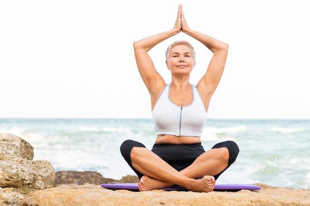 Vorderansicht ältere frau, die yoga am strand tut. kopieren sie den speicherplatz für das modell