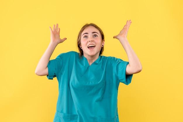Vorderansicht ärztin aufgeregt auf gelbem hintergrund gesundheitsmediziner emotionskrankenhaus