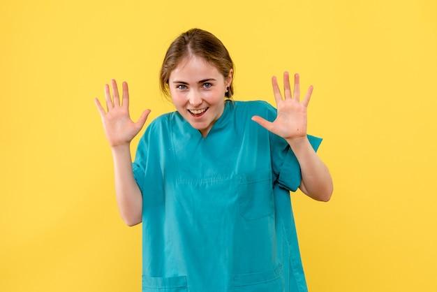 Vorderansicht ärztin aufgeregt auf gelbem hintergrund gesundheitsmediziner krankenhaus emotion