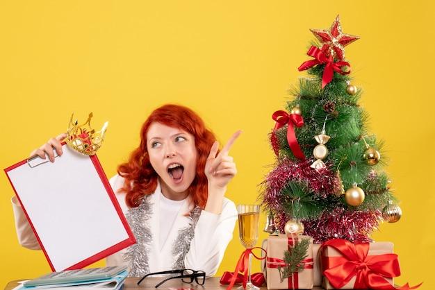 Vorderansicht ärztin, die aktennotiz um weihnachtsbaum und geschenke hält